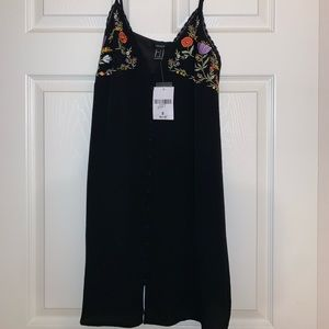 Embroidered black mini dress.